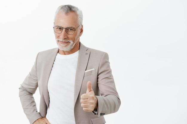 Przystojny, pomyślny starszy biznesmen pokazując kciuki do góry w aprobacie