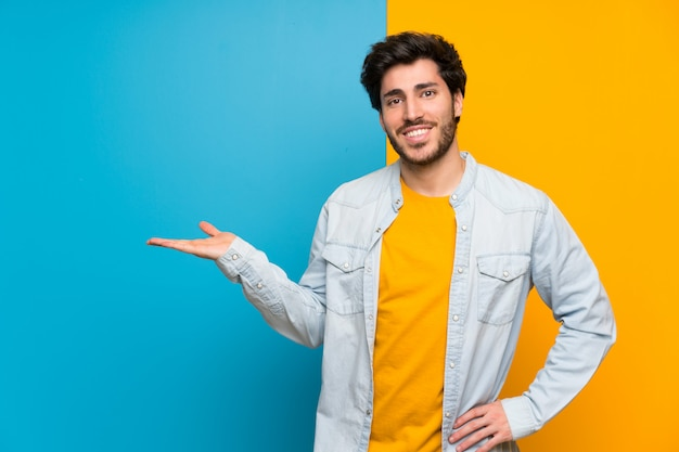 Przystojny ponad pojedyncze kolorowe gospodarstwa copyspace imaginacyjny na dłoni, aby wstawić reklamę