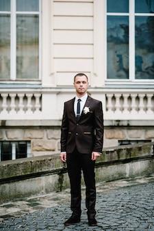 Przystojny portret pana młodego w garniturze ślubnym stoi na starym kamiennym bruk w pobliżu zabytkowego pałacu na zewnątrz, stary budynek.