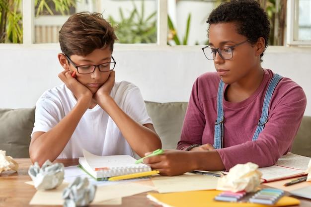 Przystojny, poważny azjatycki chłopiec ma szkolenie językowe z korepetytorem, siada razem przy biurku, odrabia zadania domowe i lekcje, skupia się na notatniku z notatkami, przygotowuje się do egzaminu wstępnego lub seminarium