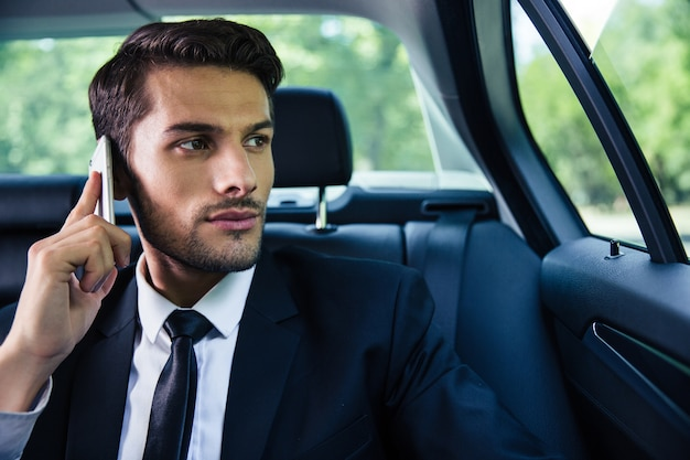 Przystojny poważny biznesmen rozmawia przez telefon w samochodzie