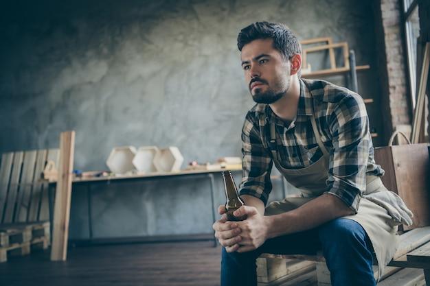 Przystojny, poważny facet trzymający butelkę piwa musi pracować za granicą, aby zarobić pieniądze tęsknić za rodziną samotne zakończenie dnia drewnianego biznesu przemysł stolarski sklep w pomieszczeniu