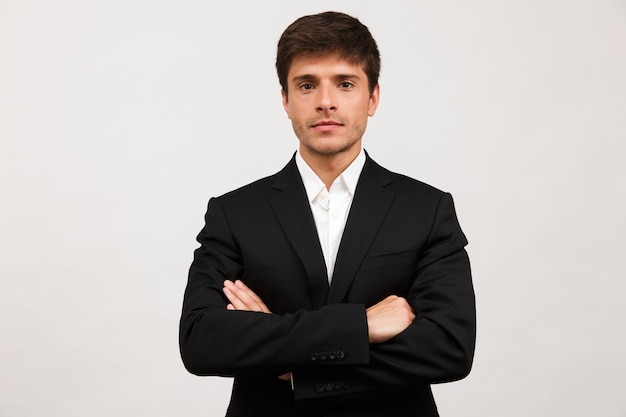 Przystojny poważny młody biznesmen stojący na białym tle na białej ścianie.
