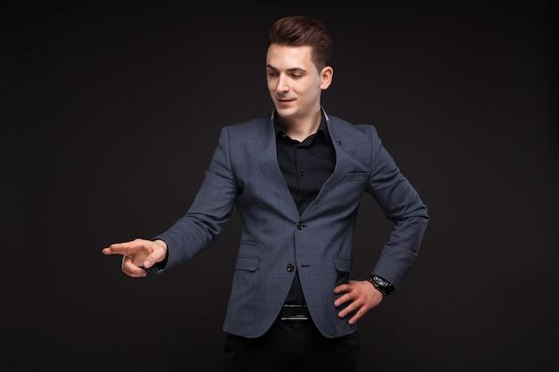 Przystojny poważny młody biznesmen w szarej kurtce, drogim zegarku i czarnej koszuli, czarna ściana