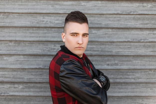 Przystojny, poważny młody mężczyzna o brązowych oczach w modnej czerwonej kraciastej kurtce z modną fryzurą w koszulce z zegarem pozuje w pobliżu zabytkowej drewnianej ściany