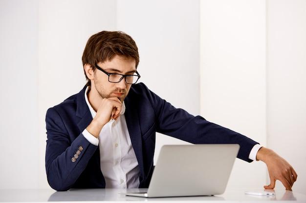 Przystojny poważny, zdecydowany biznesmen nosi okulary, czyta raport lub studiuje mapy na ekranie laptopa, pracując z biura