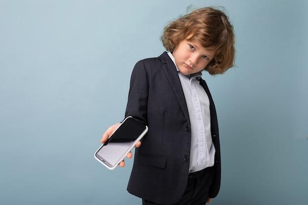 Przystojny pozytywny chłopak z kręconymi włosami, ubrany w garnitur, trzymający telefon na białym tle nad niebieskim tłem, patrzący na kamerę i pokazujący smartfona z pustym ekranem wyświetlacza
