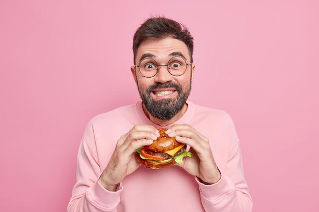 Przystojny, pozytywny facet objada się niezdrowym odżywianiem trzyma apetyczny hamburger z radością spogląda w kamerę, kusząc do jedzenia fast foodów, nosi okrągłe okulary