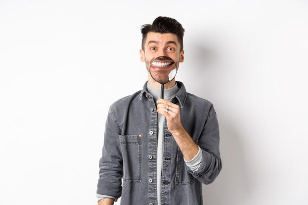 Przystojny pozytywny facet pokazujący biały idealny uśmiech z lupą, stojący na białym tle