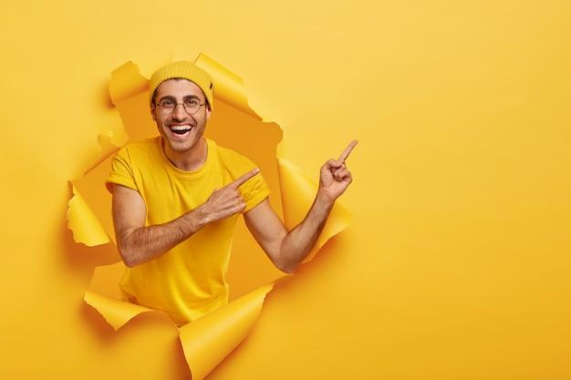 Przystojny pozytywny mężczyzna pozuje przez podarty papier