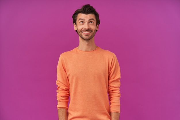 Przystojny, pozytywny mężczyzna z brunetką i włosiem. ubrana w pomarańczowy sweter z podwiniętymi rękawami
