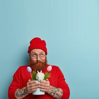 Przystojny, pozytywny mężczyzna z gęstą rudą brodą wygląda zamyślnie, myśli jak świętować wielkanoc, nosi tradycyjny króliczek w doniczce z trawą i jajkami, ma tatuaż, nosi stylowe czerwone ubranie