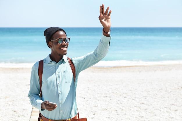Przystojny pozytywny młody człowiek w stylowych odcieniach i nakryciach głowy, podnosząc rękę