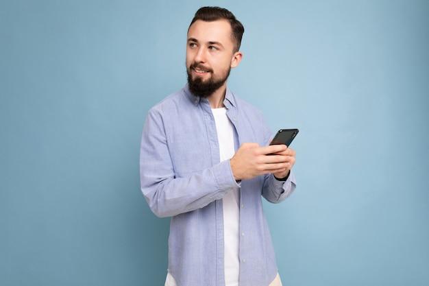 Przystojny pozytywny przystojny młody człowiek ubrany w trwały stylowy strój dorywczo