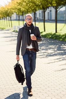 Przystojny pracownik biurowy w garniturze z szalikiem, trzymając torbę i pije kawę rano przed rozpoczęciem pracy w pobliżu budynku biurowego. młody biznesmen idzie na spotkanie biznesowe.