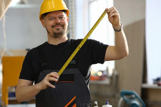 Przystojny pracownik pomiaru. praca ręczna majsterkowanie doskonalenie inspiracja praca napraw sklep żółty kask stolarka startu miejsce pracy pomysł projektant kariera władca edukacja przemysłowa