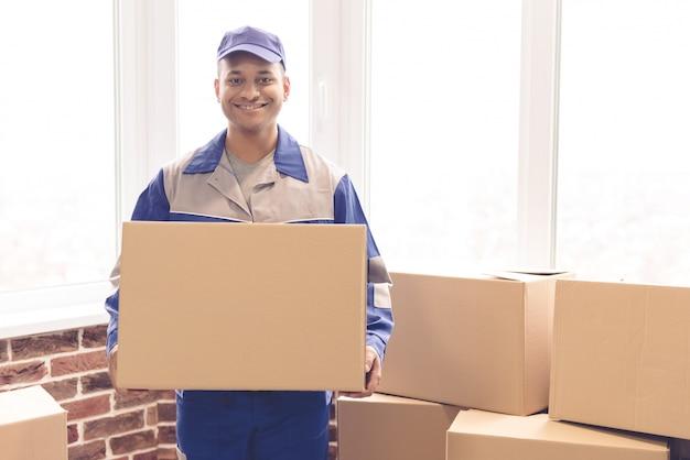 Przystojny pracownik w błękita mundurze trzyma pudełko.
