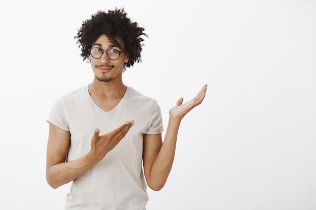 Przystojny programista w okularach, mężczyzna z uśmiechem wskazującym prawy górny róg, przedstawia produkt