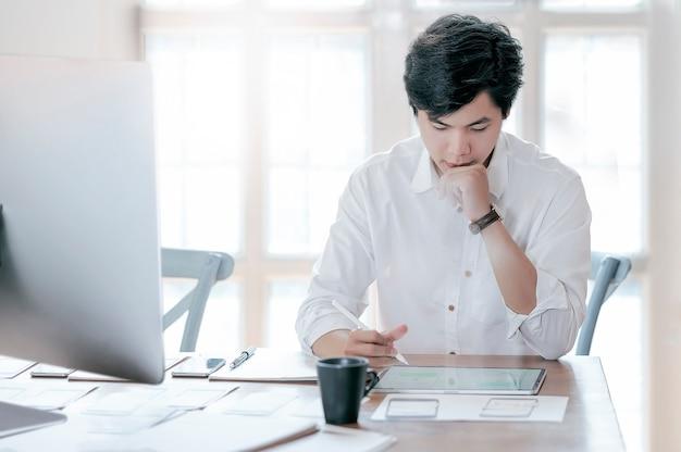 Przystojny projektant pracuje przy nowożytnym biurem.