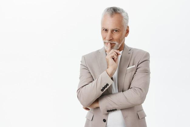 Przystojny, przebiegły starszy biznesmen uciszający, ma sekretny plan