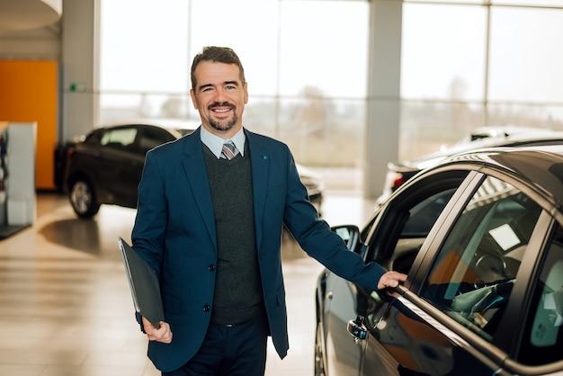 Przystojny przedstawicielstwo firmy samochodowej pracownik w kostiumu trzyma falcówkę i ono uśmiecha się
