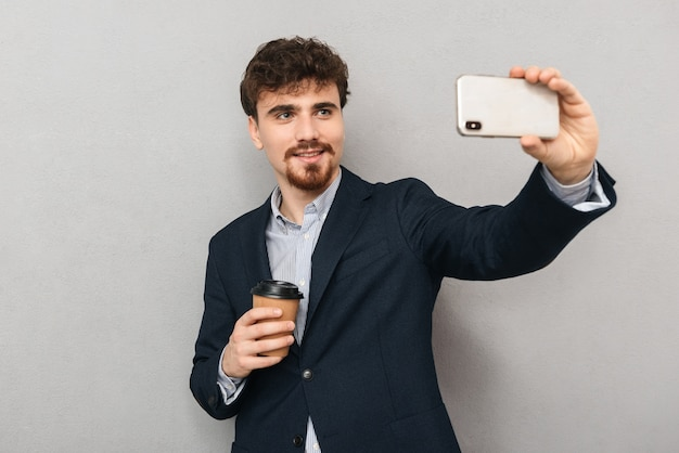 Przystojny, przekonany, młody biznesmen ubrany w kurtkę stojącą na białym tle nad szarym, biorąc selfie, trzymając kubek kawy na wynos