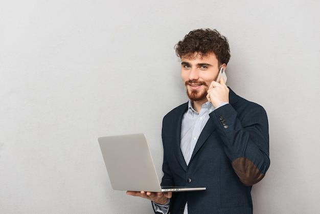 Przystojny, przekonany, młody biznesmen ubrany w kurtkę stojącą na białym tle nad szarym, pracując na komputerze przenośnym, rozmawiając przez telefon komórkowy
