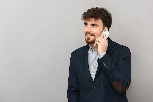Przystojny, przekonany, młody biznesmen ubrany w kurtkę stojącą na białym tle nad szarym, rozmawiając przez telefon komórkowy