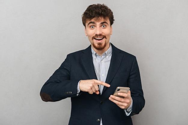 Przystojny, przekonany, młody biznesmen ubrany w kurtkę stojącą na białym tle nad szarym, trzymając telefon komórkowy