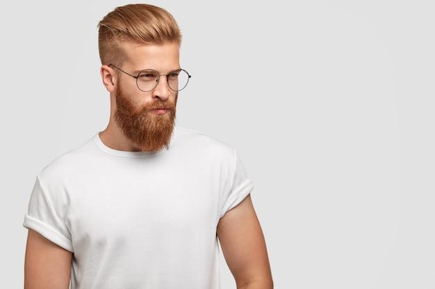 Przystojny, przemyślany, stylowy mężczyzna ma gęstą rudą brodę, zamyślony