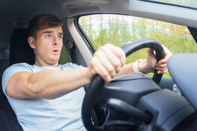 Przystojny przestraszony przerażający facet, kierowca, młody przestraszony mężczyzna zszokował się o wypadek drogowy, prowadząc samochód na drodze trzymając kierownicę samochodu. odpinany pasami bezpieczeństwa. wykroczenie drogowe