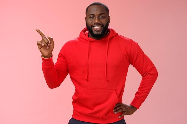 Przystojny, przyjazny czarny facet z brodą ubrany na co dzień w czerwoną bluzę z kapturem wskazującą w lewo, aby pomóc klientowi znaleźć...