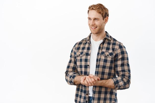 Przystojny, przyjazny rudy mężczyzna, trzymający się za ręce w grzecznych pozach, uśmiechający się i patrzący z boku na klienta lub klienta, oferuje swoją pomoc, pomagając ci, stojąc nad białą ścianą