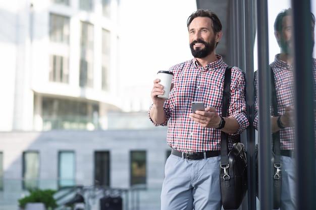 Przystojny przyjemny mężczyzna uśmiecha się podczas korzystania z telefonu na zewnątrz