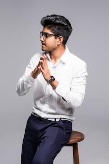 Przystojny przystojny indyjski mężczyzna siedzący na krześle i relaksujący, na białym tle na białej ścianie