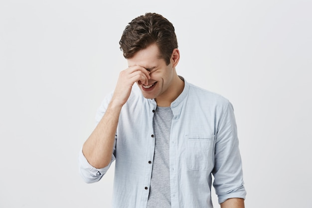 Przystojny przystojny kaukaski mężczyzna z modną fryzurą ubrany w niebieską koszulę, uśmiechnięty, śmiejący się z dowcipu przyjaciela lub zabawnej historii, dotykający grzbietu nosa. koncepcja pozytywnych emocji i reakcji.