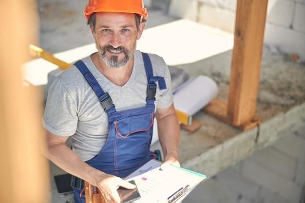 Przystojny, radosny inżynier z rysunkami i gadżetem w dłoniach uśmiechający się do kamery