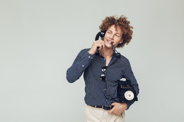 Przystojny retro mężczyzna z telefonem w rękach.