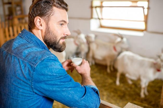 Przystojny rolnik degustacja świeżego mleka stojący w stodole kóz z kóz w tle. produkcja i hodowla mleka naturalnego