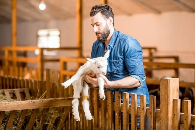 Przystojny rolnik opiekujący się uroczym koźlęciem w stodole