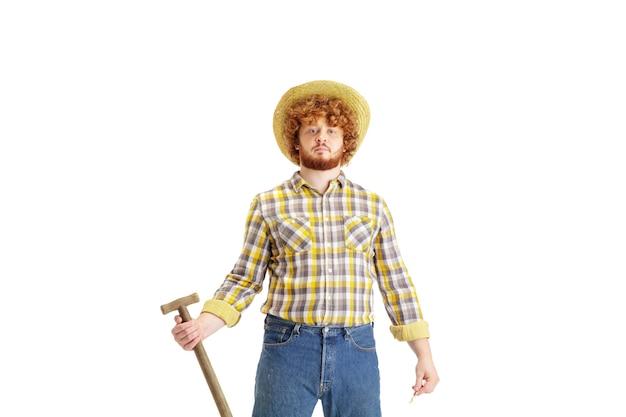 Przystojny rolnik, ranczer na białym tle nad powierzchnią białego studia. pojęcie zawodu, pracy, pracy, żywności ekologicznej. miejsce na reklamę, tekst. kaukaski mężczyzna ze sprzętem do pracy.