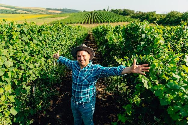 Przystojny rolnik winiarz z rękami do góry kaukaski rolnik w kapeluszu z wyciągniętymi rękami w win...