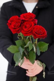 Przystojny romantyczny młody człowiek z bukietem czerwonych róż w rękach