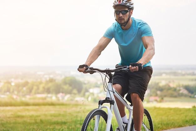 Przystojny rowerzysta na letniej jeździe na rowerze