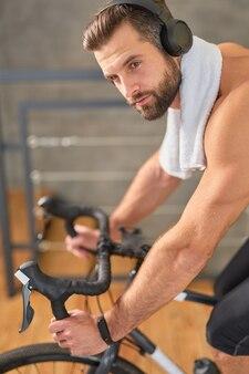 Przystojny rowerzysta w bezprzewodowych słuchawkach, cieszący się ulubionymi utworami podczas jazdy na rowerze treningowym w domu