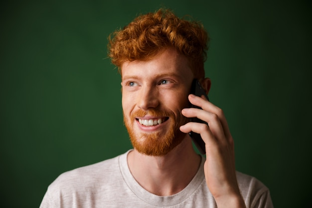Przystojny rudy brodaty mężczyzna rozmawia przez telefon