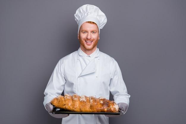 Przystojny rudy kucharz pozuje przy szarej ścianie