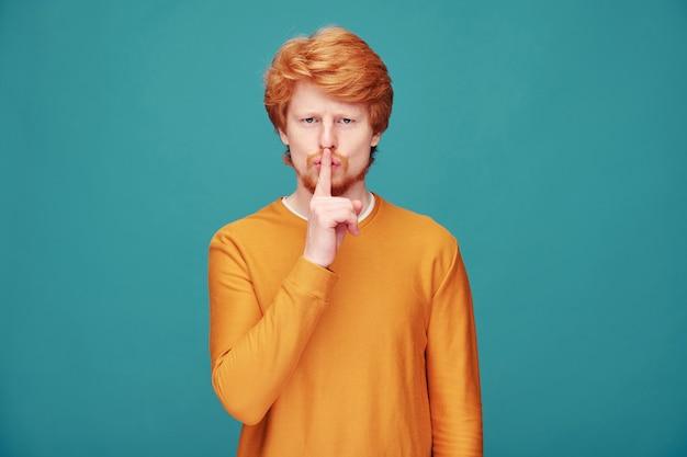 Przystojny rudy mężczyzna w pomarańczowym swetrze trzyma palec w pobliżu ust, prosząc o zachowanie spokoju