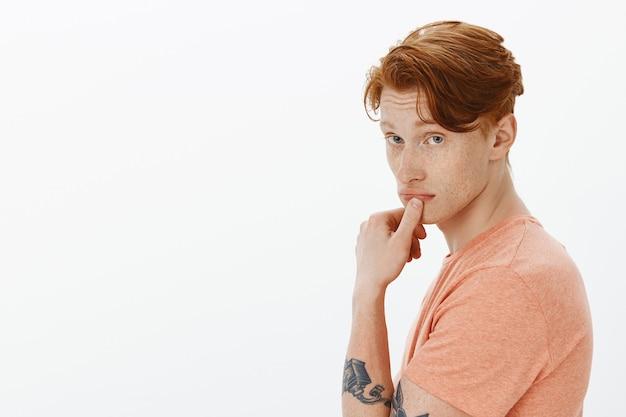 Przystojny rudy mężczyzna z tatuażami, zaintrygowany, patrząc w kamerę, myślący