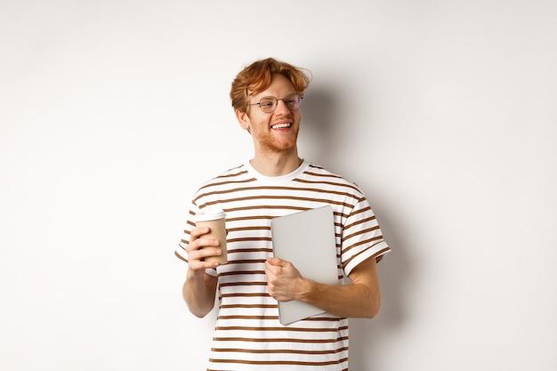 Przystojny rudy pracownik płci męskiej w okularach po przerwie, picie kawy i trzymając laptopa, stojąc na białym tle.